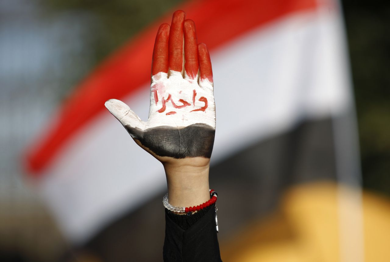 """A woman displays her hand painted with Yemen's flag and Arabic writing that reads, """"finally!"""" during a rally to show support for president Abed Rabbu Mansour Hadi, in Sanaa, Yemen, Thursday, Dec. 20, 2012. (AP Photo/Hani Mohammed)"""
