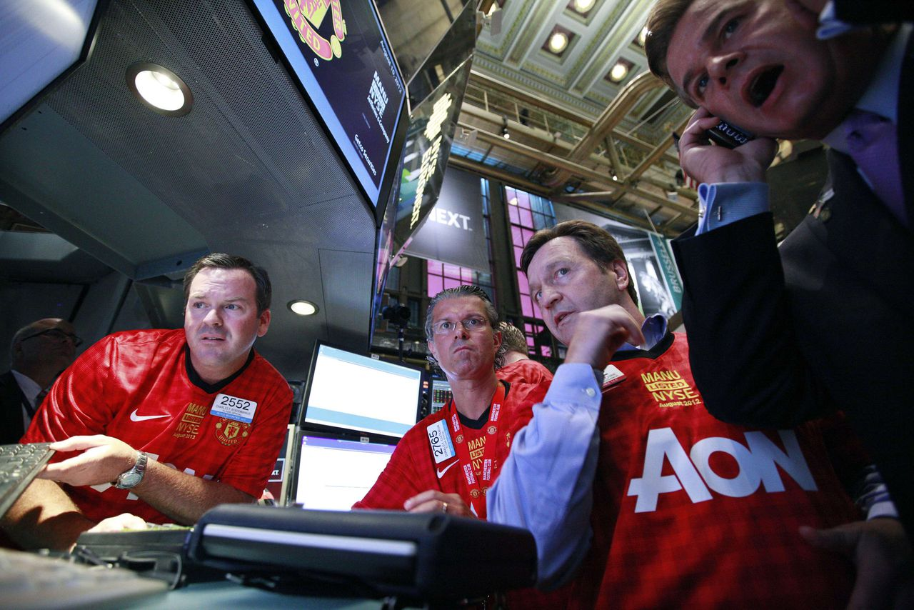 Specialists and traders from Getco Securities prepare for the start of trading of Manchester United Ltd following it's initial public offering on the floor of the New York Stock Exchange, August 10, 2012. Shares in Manchester United priced below expectations and were essentially flat in early trading on Friday, a disappointing stock market debut for the world's most famous soccer club and most valuable sporting team. REUTERS/Brendan McDermid (UNITED STATES - Tags: BUSINESS SPORT SOCCER)