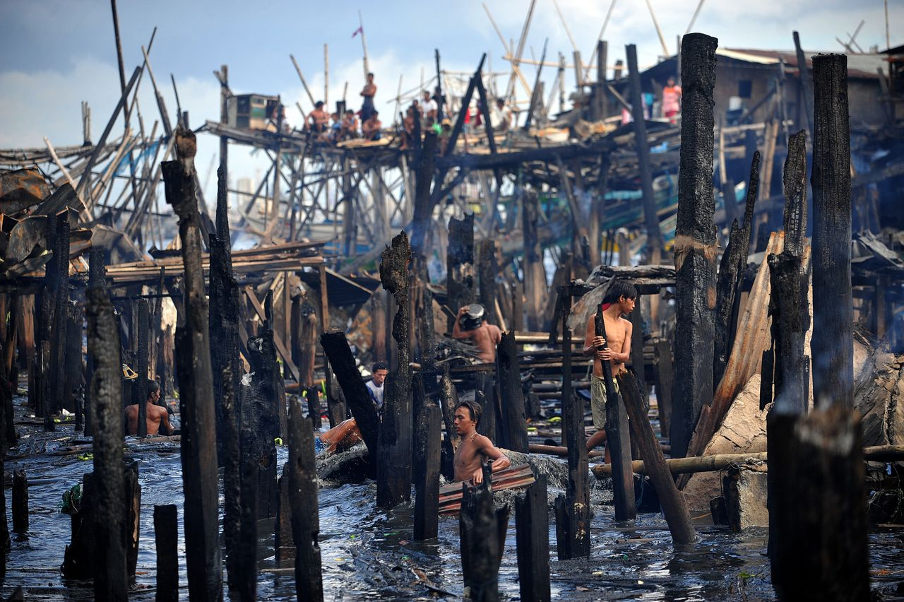 Children salvage belongings and materials from the aftermath of a fire which gutted a sprawling shanty town at the bay of Navotas, Manila on August 27, 2010. Some 200 homes were damaged, leaving around 300 families homeless, local radio reported. AFP PHOTO/NOEL CELIS