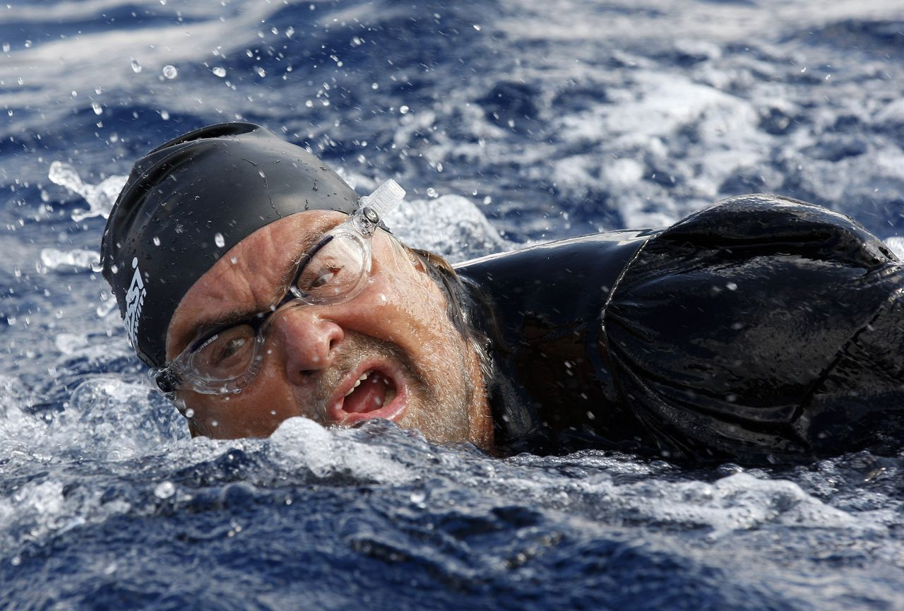 Five-Star Movement activist and comedian Beppe Grillo swims across the Strait of Messina in Sicily as he begins his election campaign October 10, 2012. Italian elections are expected to take place in spring 2013. REUTERS/Antonio Parrinello (ITALY - Tags: POLITICS ELECTIONS ENTERTAINMENT)