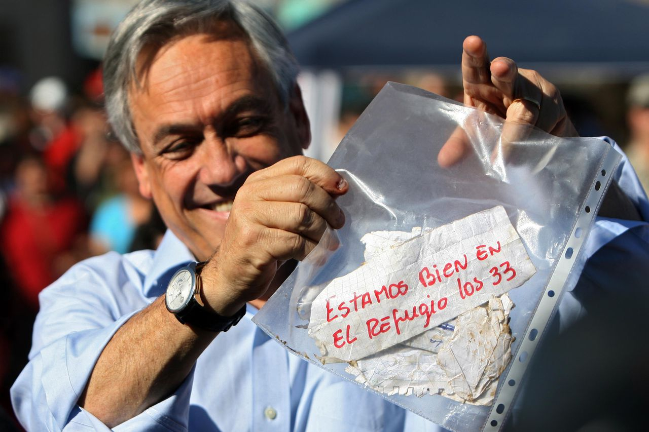 "De Chileense president toont een briefje van de kompels waarin ze lieten weren dat ze in leven zijn. Foto AFP Chilean President Sebastian Pinera shows a message reading ""We are fine in the refuge, the 33 of us"", from the miners trapped in the San Esteban gold and copper mine, near the city of Copiapo, Atacama desert, 800 km (480 miles) north of Santiago, on August 22, 2010. The miners are alive and contact has been established with them 17 days after a structural collapse trapped them below ground. AFP PHOTO/ HECTOR RETAMAL"