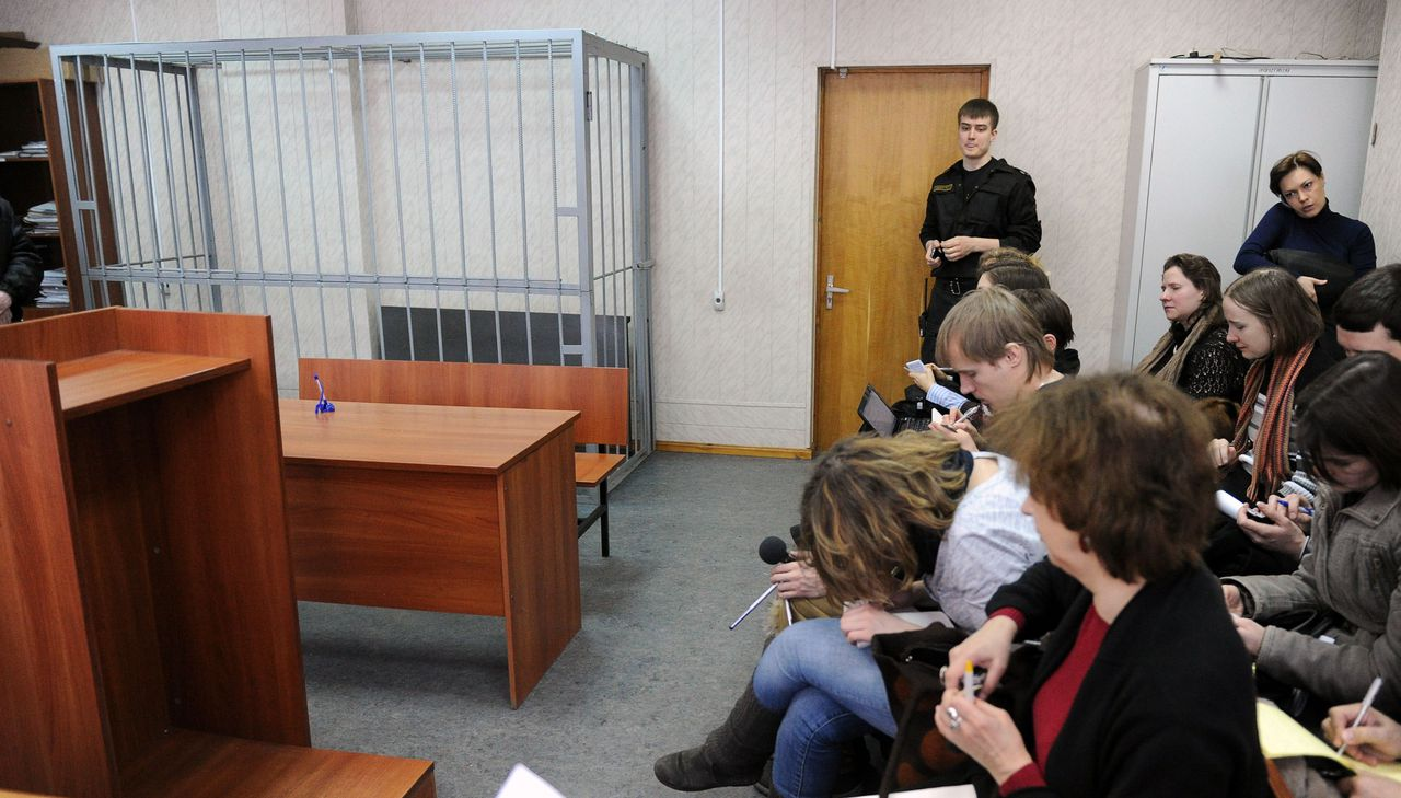 Journalists sit next to the empty defendant's cage in the Tverskoy district court of Moscow on March 27, 2013, during a hearing in the posthumous trial of lawyer Sergei Magnitsky for tax evasion, days after Russia closed a probe into the circumstances of his prison death. AFP PHOTO / ANDREY SMIRNOV