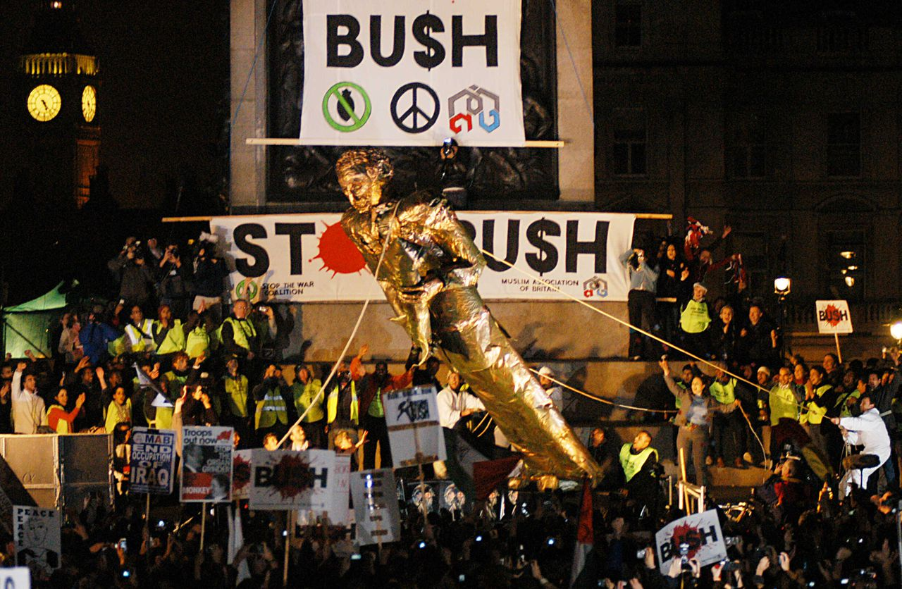 """De symbolische 'val' van George Bush in Londen, 2003. Foto AFP Anti-Bush protesters topple a statue of US President George W. Bush during a """"STOP BUSH"""" protest organised by the Stop the War coalition in central London 20 November 2003. The coalition is protesting the state visit of Bush to Britain and the war in Iraq. AFP PHOTO/EVA-LOTTA JANSSON"""
