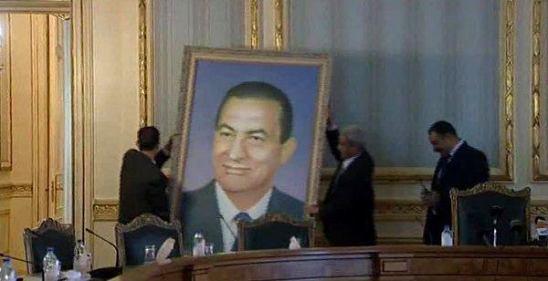Een portret van Mubarak wordt weggehaald uit het regeringsgebouw in Kairo.