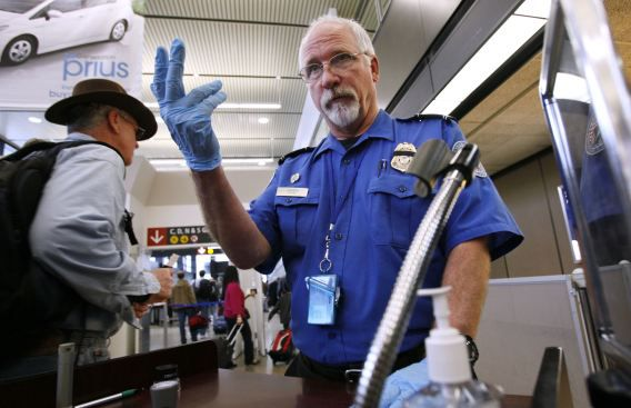 Een beveiligingsmedewerker op het internationale vliegveld in Seattle-Tacoma maant de volgende reiziger in de rij naar voren te komen voor een controle.