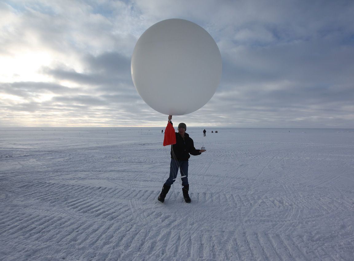 In this July 15, 2011 photo, atop roughly two miles of ice, technician Marie Mclane launches a data-transmitting weather balloon at Summit Station, a remote research site operated by the U.S. National Science Foundation (NSF), and situated 10,500 feet above sea level, on top of the Greenland ice sheet. Across Greenland's vast white landscape, small teams of researchers from around the world are searching for clues to the potential effects of global warming on Greenland's ice. (AP Photo/Brennan Linsley)
