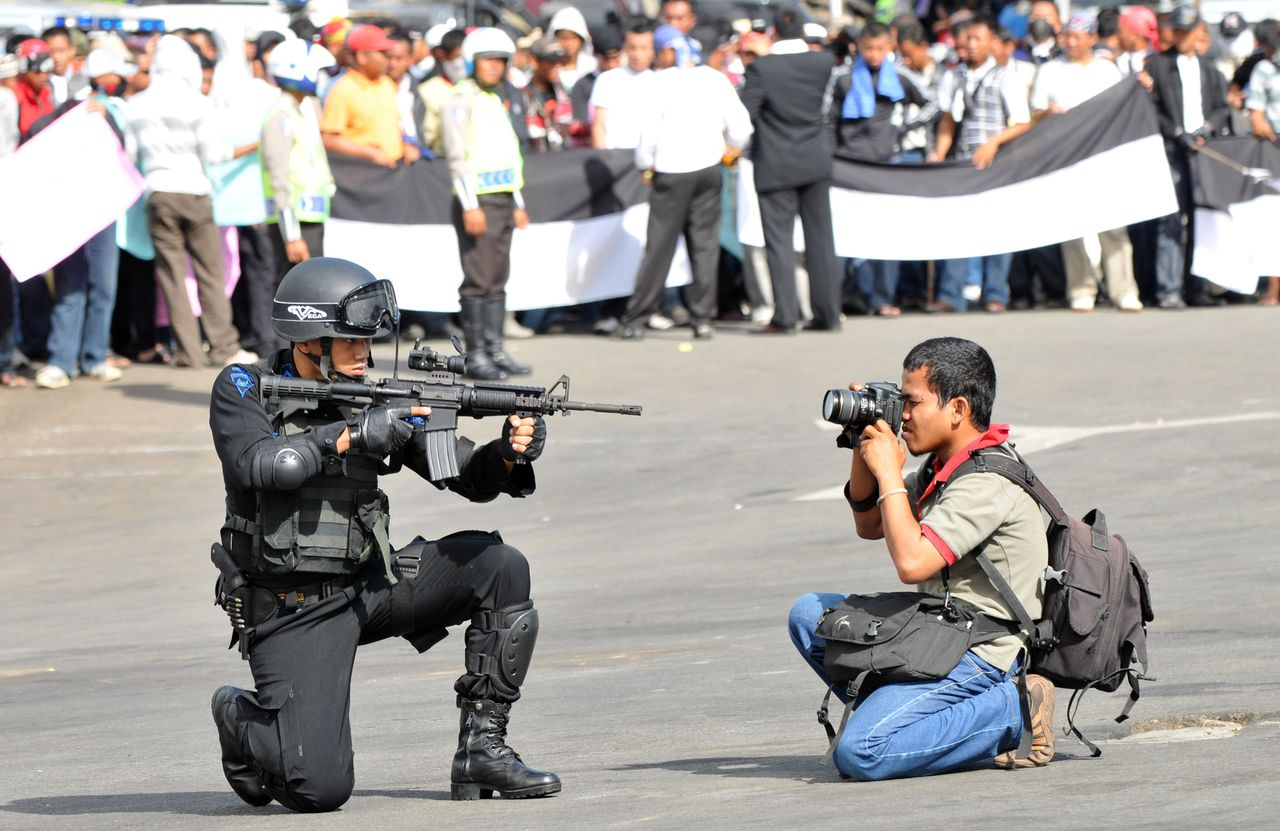 Jakarta, Indonesië, 4 maart 2009 (Foto AFP) An Indonesian photographer takes pictures of an Indonesian anti-terror policeman during a security drill for the next elections in Jakarta on March 4, 2009. Indonesia will hold the parliamentary elections on April 9 and the first round presidential elections on July 8. AFP PHOTO/ADEK BERRY