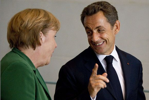 Caption: German Chancellor Angela Merkel shares a smile with French President Nicolas Sarkozy as they arrive to give a statement on October 9, 2011 at the Chancellery in Berlin following a key summit on steps to combat debt turbulence in the Eurozone. The leaders of Europe's two biggest economies are expected in particular to try to hammer out details of a plan to recapitalise Europe's banks amid fears of a crippling credit crunch. AFP PHOTO ODD ANDERSEN
