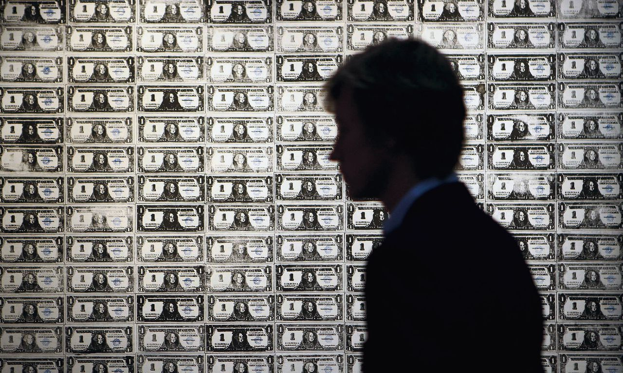 """FILE - In this Oct. 12, 2009 file photo, a visitor stands in front of a painting """"200 One Dollar Bills,"""" by Andy Warhol on display at the auction house in London. Warhol painting called """"200 One Dollar Bills"""" has sold at auction for $43.8 million, ($29.3 million euro) more than three times its highest presale estimate of $12 million. (AP Photo/Sang Tan, File)"""