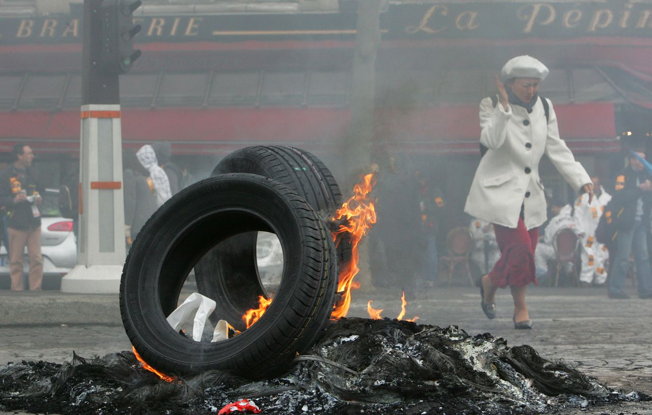 Al twee maanden lang voeren werknemers bij het bandenconcern Continental in het Noord-Franse Clairoix actie tegen de aangekondigde sluiting van hun fabriek. Foto AP A woman covers her face as she walks near a pile of burning tires, as Continental employees, unseen, of the Clairoix tire plant, northern France, demonstration Wednesday March 25, 2009 in Paris. Workers at the factory, which employs 1,120, agreed in 2007 to a 40-hour work week, up from France's standard 35-hour week, to boost productivity and keep the site open. German auto parts and tire company Continental AG recently said it would stop producing tires at its plant in Clairoix and reduce capacity at other sites in Europe, laying off workers as a result. (AP Photo/Jacques Brinon) brandende autobanden op straat