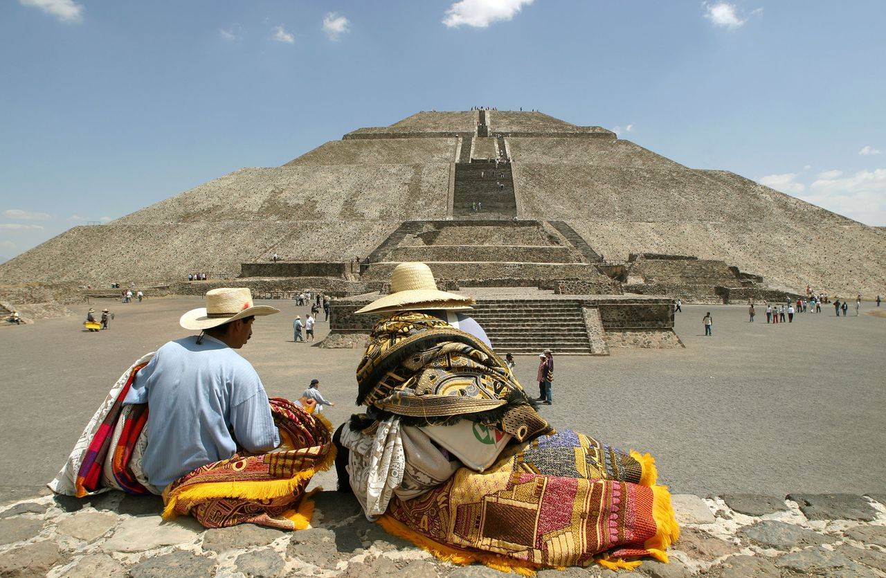 """Verkopers bij de piramide van de Zon bij Teotihuacan, 60 km boven Mexico-stad. Foto Reuters Two vendors sit near the pyramid of the Sun at Teotihuacan 60km (36 miles) north of Mexico City, in this March 9, 2004 photo. Deep under the huge Pyramid of the Sun north of Mexico City, physicists are installing a device to detect """"muons,"""" sub-atomic particles left over when cosmic rays hit earth. The particles pass through solid objects, leaving tiny traces which the detector will measure, like an X-ray machine, in a search for burial chambers inside the monolith. REUTERS/Daniel Aguilar/FEATURE MEXICO-ARCHEOLOGY DA/HB"""