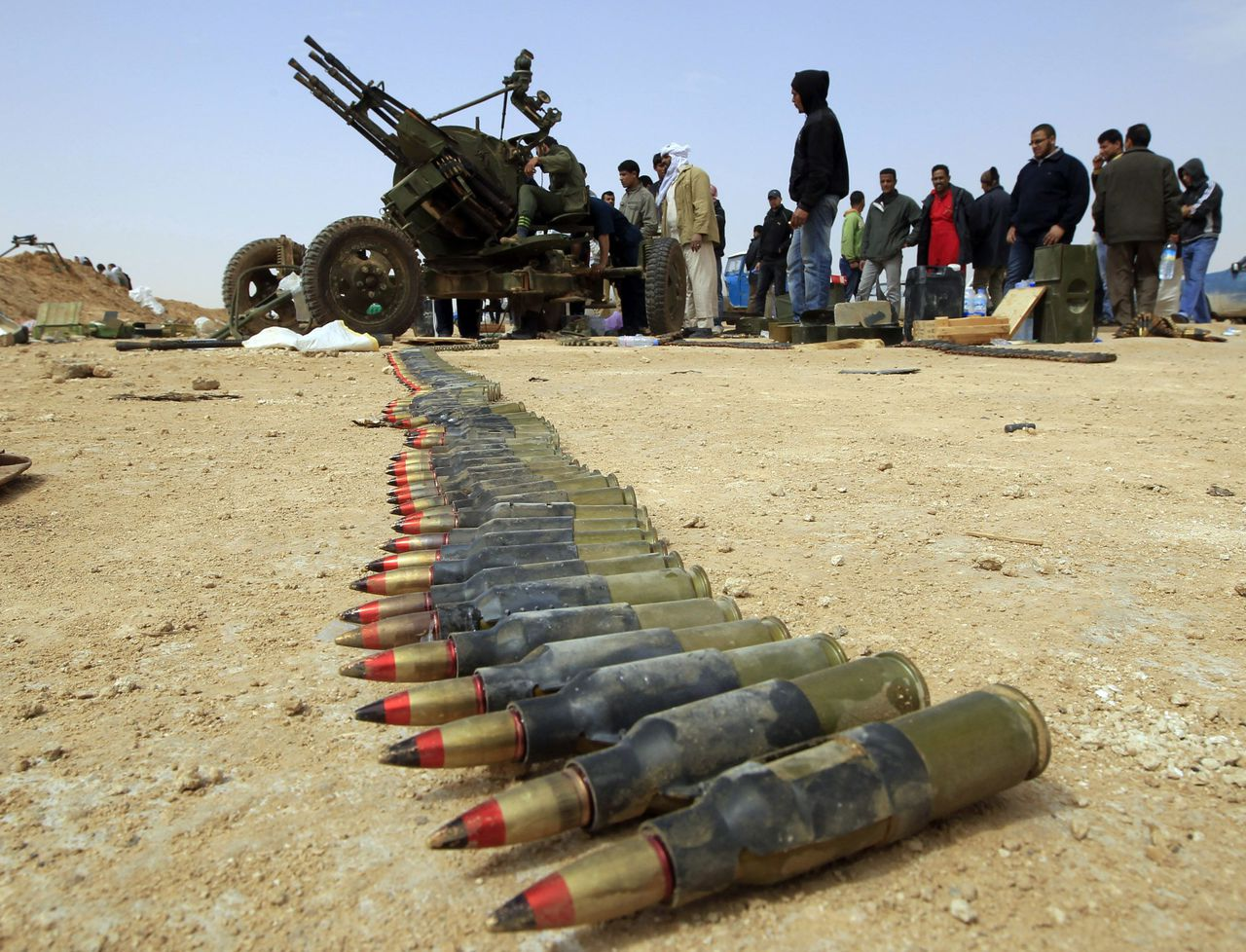 Rebels stand around an antiaircraft weapon on the outskirts of Ajdabiya, on the road leading to Brega, March 2, 2011. REUTERS/Goran Tomasevic (LIBYA - Tags: POLITICS CIVIL UNREST MILITARY)