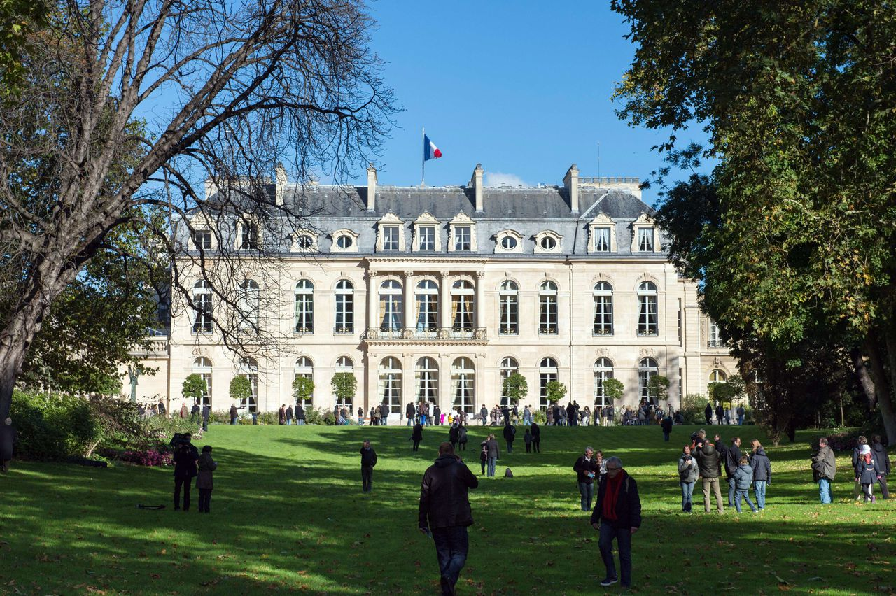 people walk around the gardens of the Elysee presidential palace in Paris on October 28, 2012. The Elysee gardens are now open to the public on the last Sunday of each month . AFP PHOTO BERTRAND LANGLOIS