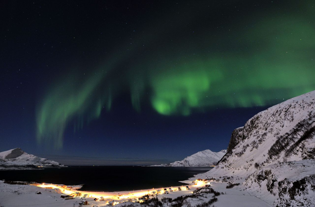 In this photo taken Sunday, Feb. 13, 2011, the aurora borealis, or northern lights, light up the sky above the village of Grotfjord, near Tromso, northern Norway. (AP Photo/Keystone, Martial Trezzini) NO SALES, NO ARCHIVE