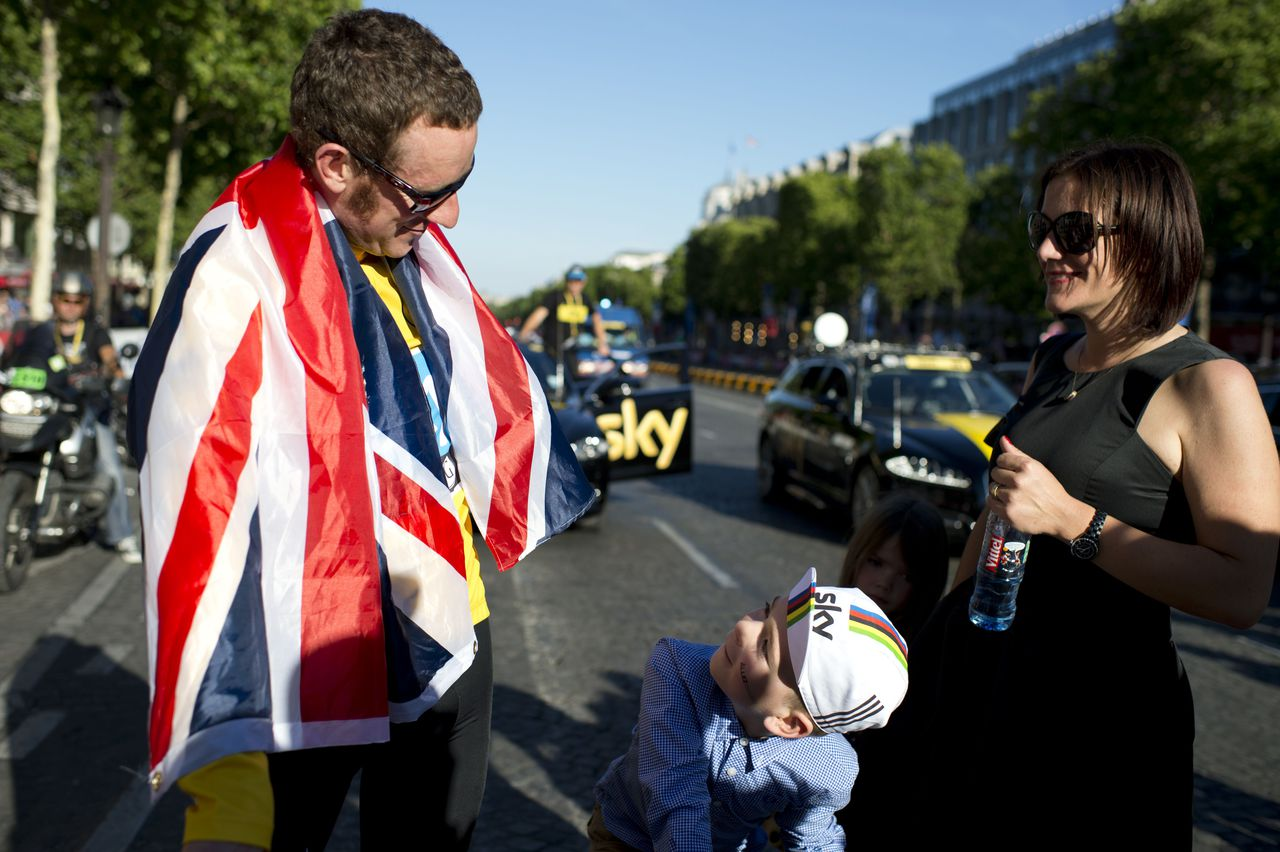 Tour de France 2012 winner, Yellow jersey British Bradley Wiggins, (L), wrapped in a national flag, looks at his son as his wife Catherine looks on, during a parade on the Champs-Elysees Avenue at the end of the 120 km and last stage of the 2012 Tour de France cycling race starting in Rambouillet and finishing in the famous Paris-Champs-Elysees Avenue, on July 22, 2012. AFP PHOTO / JEFF PACHOUD
