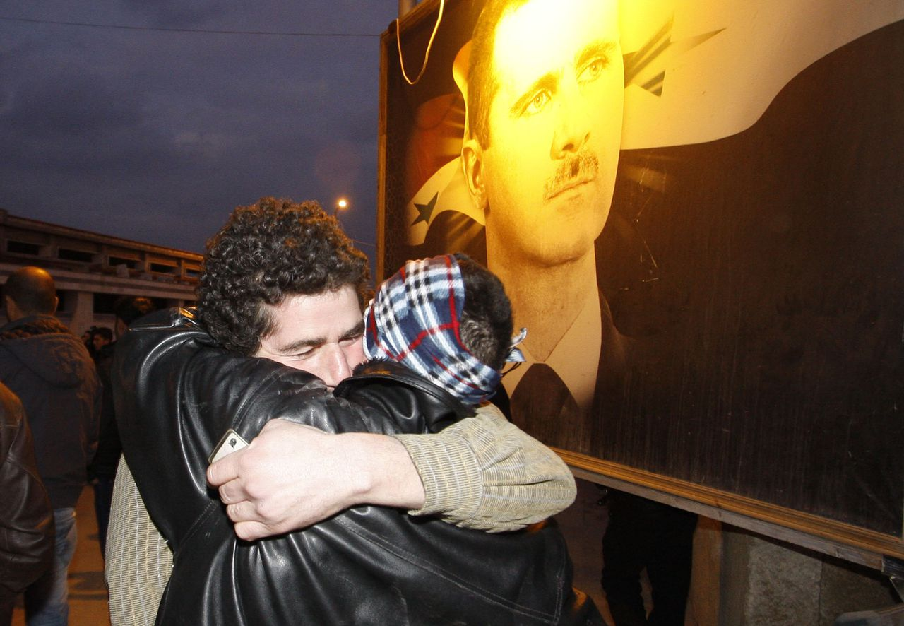 A freed Syrian prisoner, left, hugs his brother, right, after being released from Adra Prison on the northeast outskirts of Damascus, Syria, on Monday Jan. 16, 2012. Syria's state news agency SANA said on Sunday President Bashar Assad has granted a general amnesty for crimes committed during the unrest of the past 10-months. SANA said the amnesty issued Sunday covers those who have peacefully demonstrated, those who have carried unlicensed weapons and those who hand over their weapons to authorities before the end of January. (AP Photo/Muzaffar Salman)