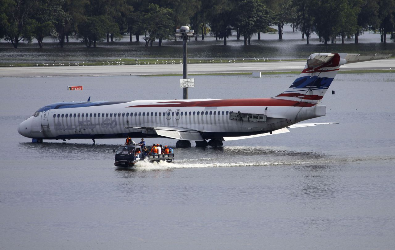 Thai workers on a truck pass by an airplane at the flooded Don Muang Airport in Bangkok, Thailand on Friday, Oct. 28, 2011. The Chao Phraya river coursing through the capital swelled to record highs Friday, briefly flooding riverside buildings and an ornate royal complex at high tide amid fears that flood defenses could break and swamp the heart of the city. (AP Photo/Aaron Favila)