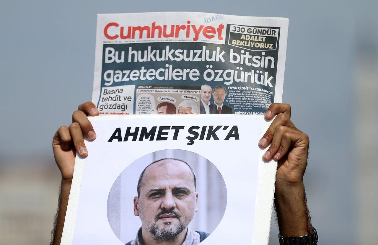 Een man houdt in september de krant Cumhuriyet omhoog met daaronder een afbeelding van journalist Ahmet Sik.