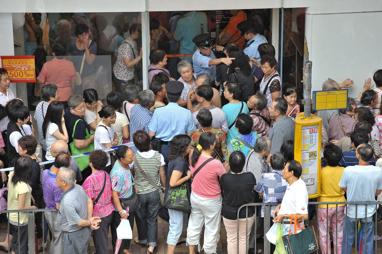 """Hongkongse spaarders stroomden woensdag al naar de Bank of East Asia om hun geld weg te halen. Foto AFP Policemen (C-in blue shirts) try to assist customers as they crowd the entrance of a branch of Hong Kong's Bank of East Asia (BEA) on September 24, 2008 after rumours believed to be related to BEA's exposure to assets linked to failed investment bank Lehman Brothers and insurance giant AIG were reported in the local press. BEA moved to quell the rumours about its stability, stating """"the management of BEA hereby states in the strongest possible terms that such rumours have no basis in fact."""" AFP PHOTO/MIKE CLARKE"""