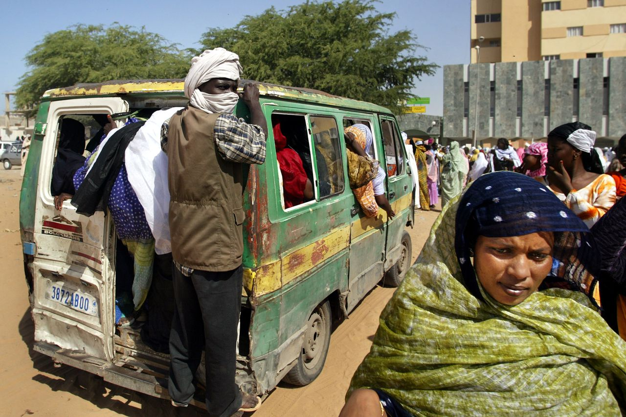 Een zwarte Mauretaniër rijdt achter op een minibus mee in de hoofdstad Nouakchott. De zwarte gemeenschap blijft leverancier van slaven. Foto AP An ethnically black-African man riding on the back of a minibus looks towards an Arab-African woman in the MAuritanian capital Noakchott in this Monday, Nov. 3, 2003 photo. Enduring Arab-African slavery along ancient Saharan trade routes, is being played out at its most extreme in Sudan's Darfur, with murderous results: Arab horseman clutching AK-47s razing non-Arab African villages and driving off and killing the villagers. (AP Photo/Ben Curtis)