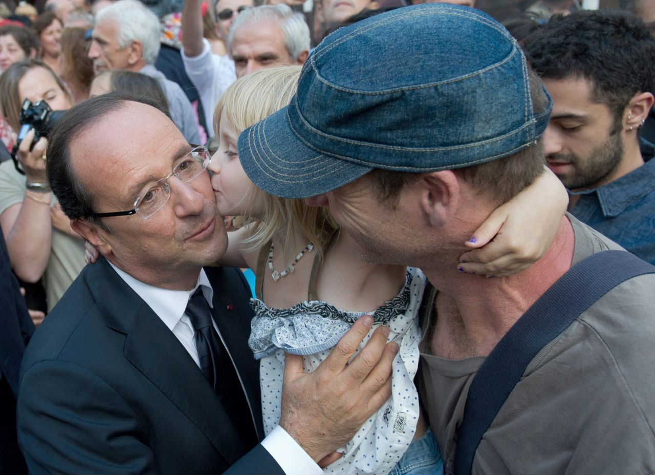 France's President Francois Hollande (L) is kissed by a young fan as he leaves the Jean Vilar (French legendary theater director, 1912-1971) house on July 15, 2012 in Avignon, southern France, during a visit at the 66th Avignon Theatre Festival. AFP PHOTO BERTRAND LANGLOIS