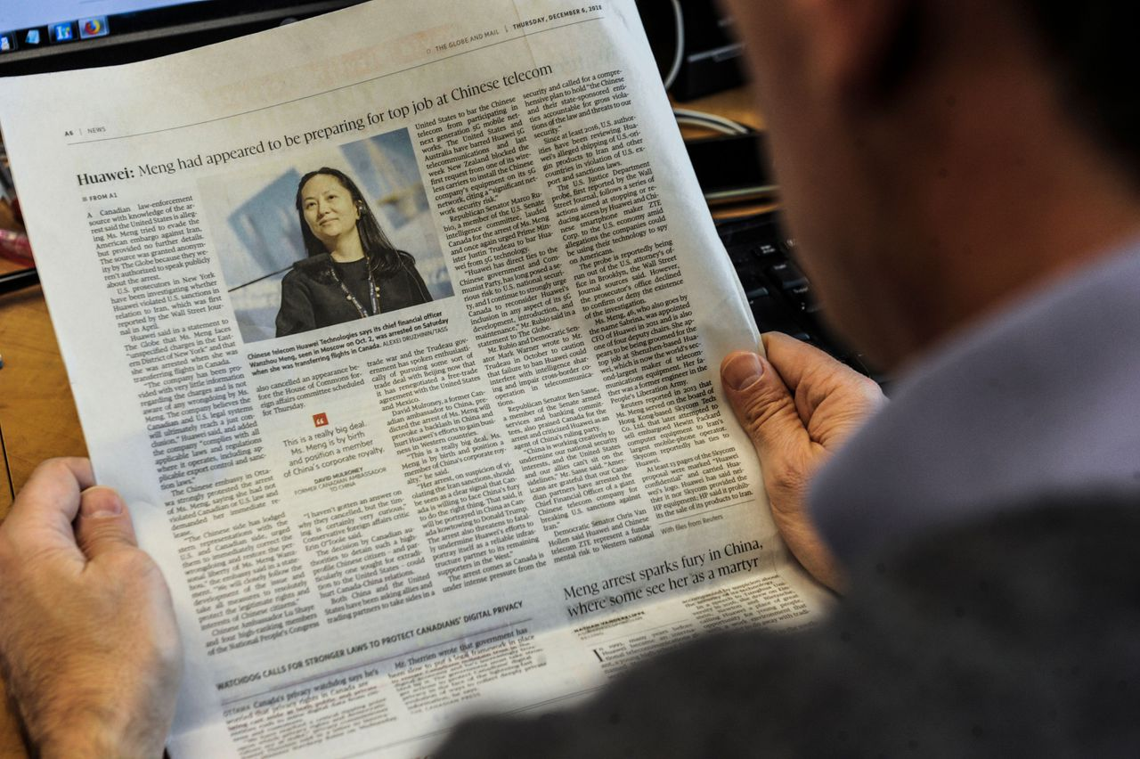 Een journalist leest de Canadese krant 'The Globe and Mail' over de arrestatie van Meng Wanzhou