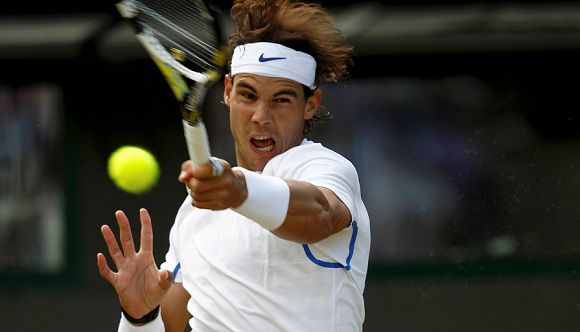 Caption: Rafael Nadal of Spain hits a return to Mardy Fish of the U.S. during their quarter-final match at the Wimbledon tennis championships in London June 29, 2011. REUTERS/Eddie Keogh (BRITAIN - Tags: SPORT TENNIS)