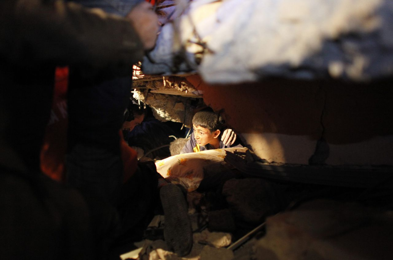Yunus, a 13-year-old earthquake survivor, waits for to be rescued from under a collapsed building by rescue workers in Ercis, near the eastern Turkish city of Van, early October 24, 2011. More than 100 people were confirmed killed and hundreds more feared dead on Sunday when a powerful earthquake hit southeast Turkey, flattening buildings and leaving survivors crying for help from under the rubble. REUTERS/Umit Bektas (TURKEY - Tags: DISASTER ENVIRONMENT TPX IMAGES OF THE DAY)