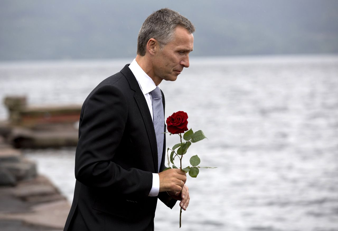 Norway's Prime Minister Jens Stoltenberg holds a flower on his way to the wreath laying ceremony at Utoeya Island on July 22, 2012, with members of the Labor Youth of Norway (AUF), guests and relatives of those who died a year ago. Norway marked the first anniversary of attacks by right-wing extremist Anders Behring Breivik, who killed 77 people in Oslo and on Utoeya Island on July 22, 2011. AFP PHOTO / DANIEL SANNUM LAUTEN