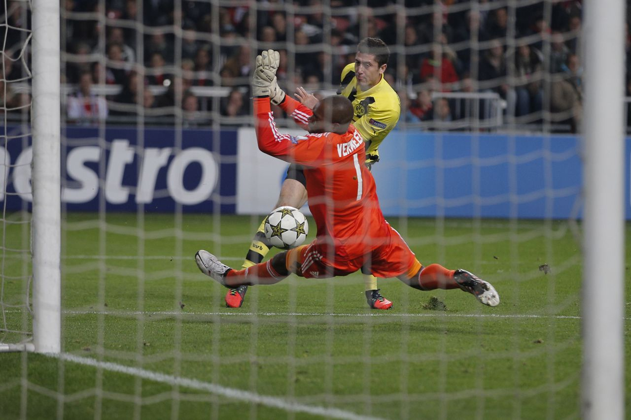 Borussia Dortmund player Robert Lewandowski scores 4-0 passing Ajax goalkeeper Kenneth Vermeer during the Champions League Group D soccer match at ArenA stadium in Amsterdam, Netherlands, Wednesday Nov. 21, 2012. (AP Photo/Peter Dejong)