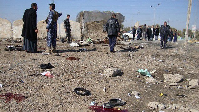 Iraqi onlookers and policemen inspect the spot where a suicide bomber blew himself up among a crowd of police recruits on January 18, 2011 in the Iraqi city of Tikrit, killing 50 people in the bloodiest attack in more than two months. AFP PHOTO/MAHMUD SALEH