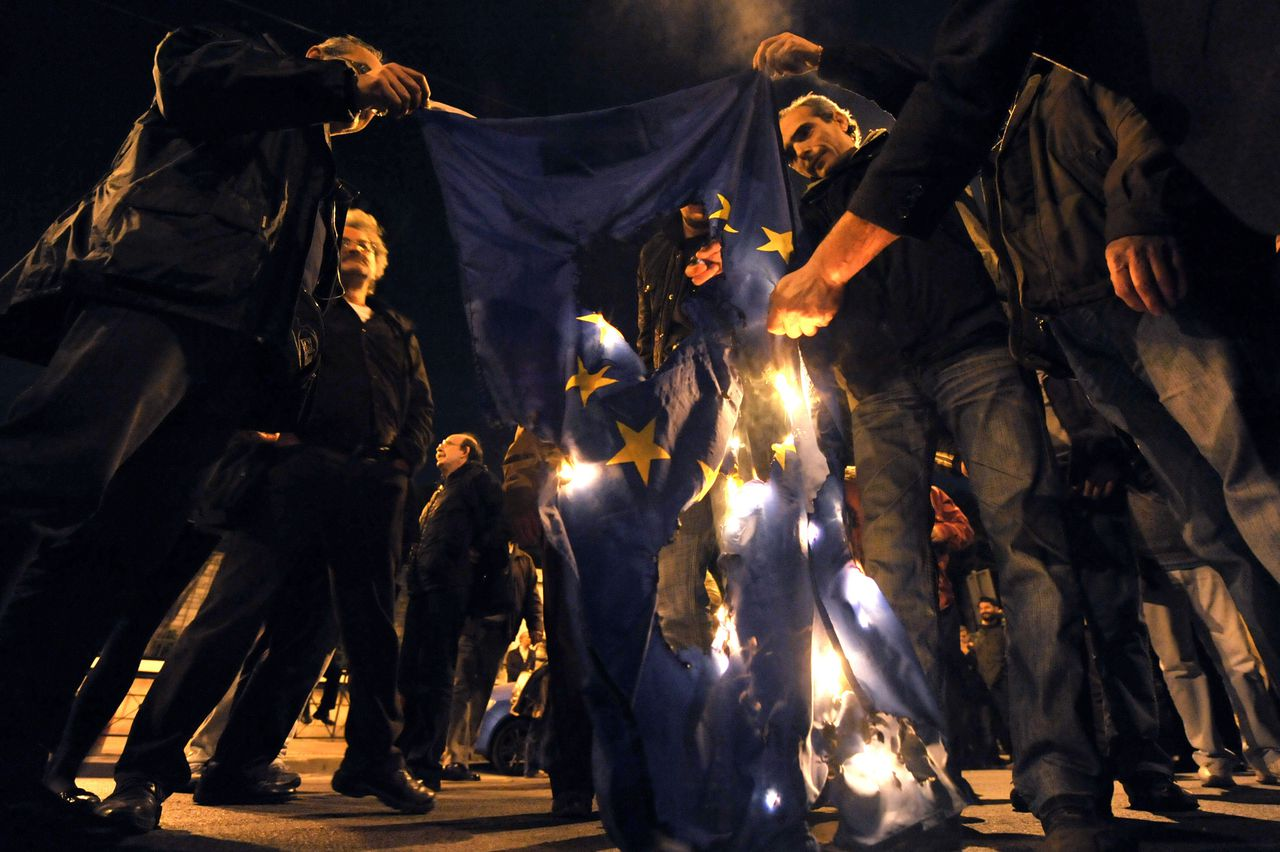 Veel Grieken zijn boos over Europese druk om te bezuinigen en het begrotingstekort te verkleinen. Foto AFP Protestors burn an EU flag near the EU offices in Athens, during a march on March 4, 2010 to protest against harsh austerity measures announced by the government. Greece has frozen pensions and raised a string of taxes to cut spending by 4.8 billion euros in a frantic bid to persuade its EU partners and the markets that it can dodge bankruptcy AFP PHOTO / Louisa Gouliamaki