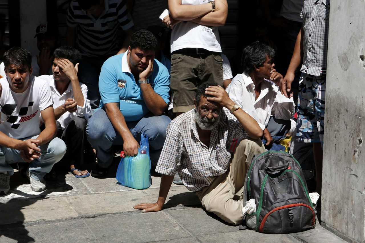 Immigrants wait to be transported to a police station in Athens August 5, 2012. Thousands of immigrants were transferred to police stations for documentation checks during an extensive operation in neighbourhoods at the centre of the Greek capital, according to the Ministry of Public Order. REUTERS/Yorgos Karahalis (GREECE - Tags: CRIME LAW SOCIETY IMMIGRATION POLITICS)