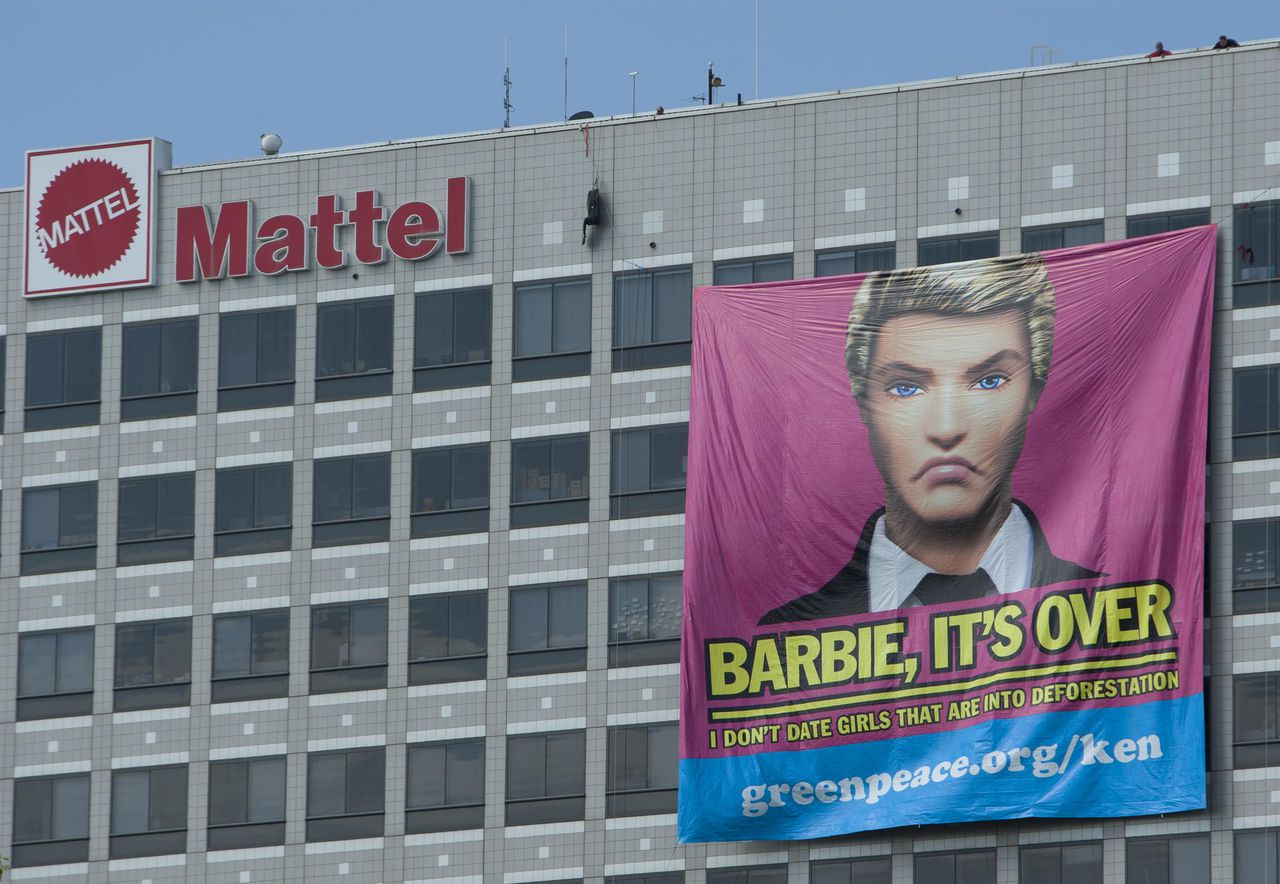 """Greenpeace activists dressed as """"Ken"""" dolls hang a huge banner off the Mattel headquarters in Los Angeles. With a clear message to their former girlfriend: """"Barbie It's Over. I Do Not Date Girls Who Are Into Deforestation."""" Greenpeace investigators have found that the toymaker Mattel is using packaging made from Asia Pulp and Paper (APP). APP has been exposed many times for wrecking Indonesia's rainforests to make products such as packaging."""