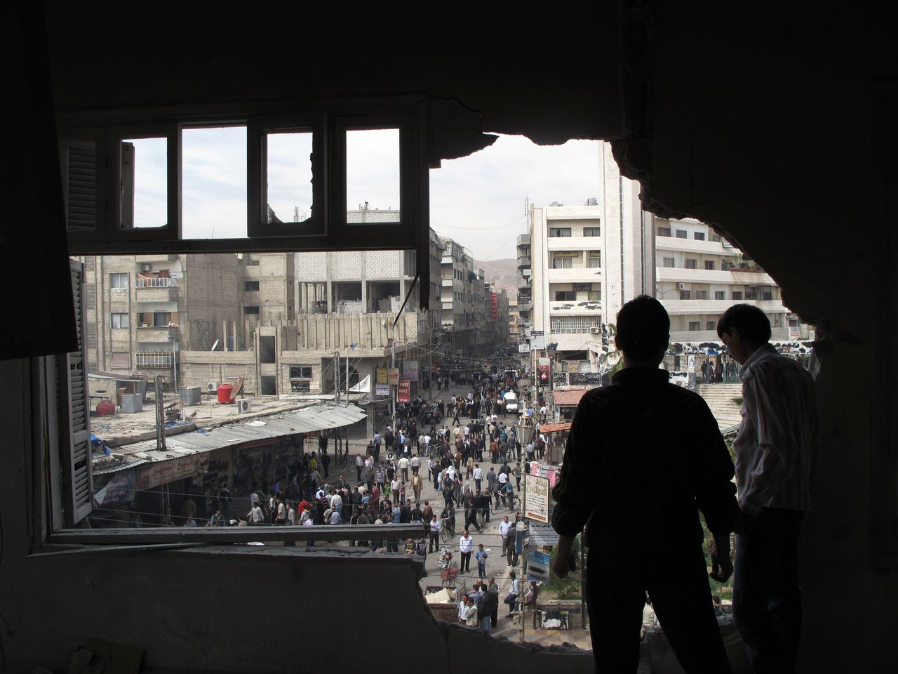 Syrian youth stand in a building damaged by tank shells in a neighborhood of Damascus, Syria, after a raid by Syrian troops killed several rebels and civilians Thursday, April 5, 2012. Syrian troops launched a fierce assault Thursday, days ahead of a deadline for a U.N.-brokered cease-fire, with activists describing it as one of the most violent attacks around the capital since the year-old uprising began. (AP Photo)