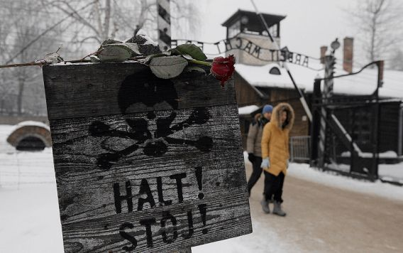 "A rose is placed on top of a sign that reads ""Stop"" with a skull painted, near the gate at the concentration camp during a ceremony marking the 68th anniversary of the liberation of the Auschwitz by Soviet troops and to remember the victims of the Holocaust, in Auschwitz Birkenau in Oswiecim, Poland, Sunday, Jan. 27, 2013. (AP Photo/Czarek Sokolowski)"