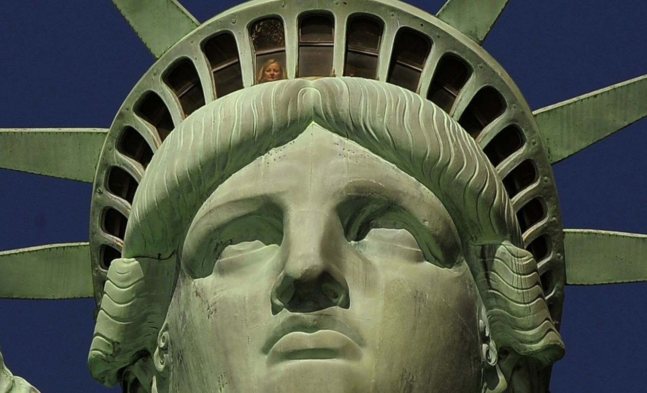 A woman looks out from the crown of the Statue of Liberty after ceremonies on Liberty Island in New York on October 28,2011 to commemorate the 125th anniversary of the dedication of the Statue of Liberty. AFP PHOTO / TIMOTHY A. CLARY