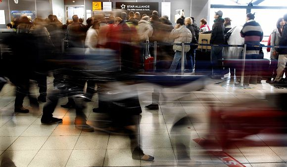 Caption: Passengers wait at an airline counter after all outgoing flights were canceled by an ongoing strike at Lyon-Saint Exupery airport, central France, Saturday, Dec. 17, 2011. Departing flights were canceled on Saturday, as a strike by security agents enters its second day. (AP Photo/Laurent Cipriani)