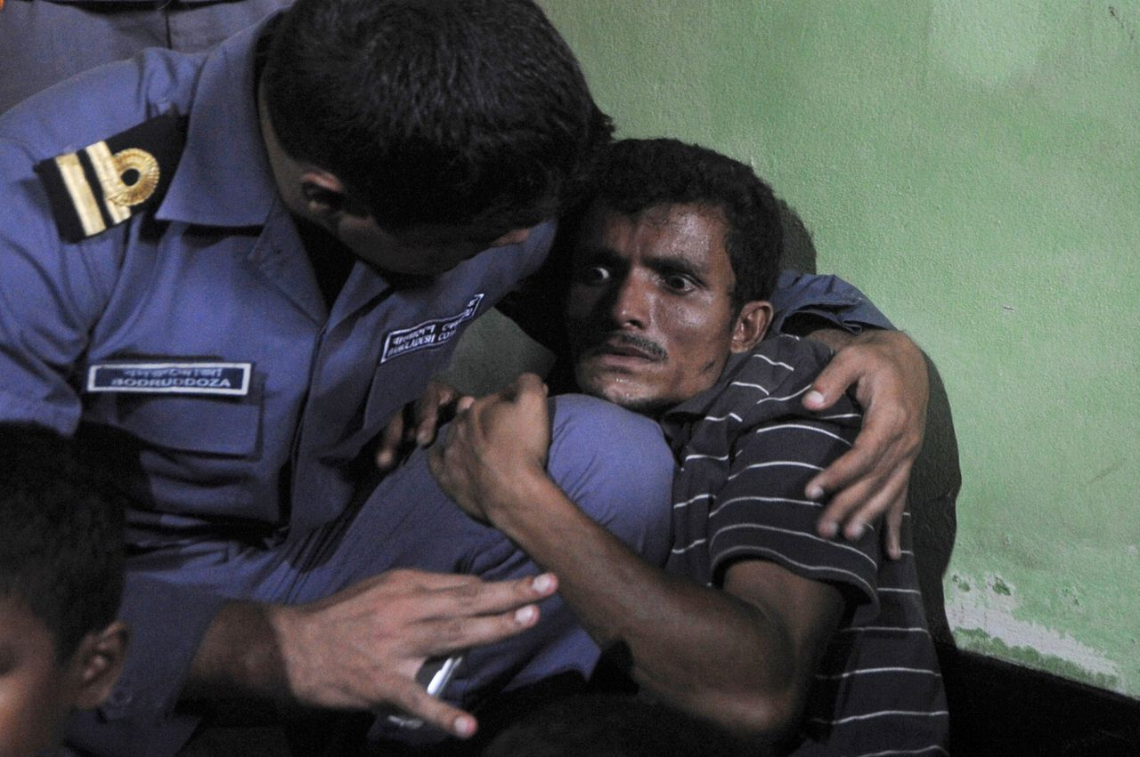 TOPSHOTS A Rohingya Muslim from Myanmar (R), who tried to cross the Naf river into Bangladesh to escape sectarian violence, cries near his family in a Bangladeshi Coast guard station in Teknaf on June 19, 2012, before being sent back to Myanmar. Bangladesh is coming under increasing international pressure to open its border to Rohingya's fleeing the violence, but has so far refused to do so. AFP PHOTO/ Munir uz ZAMAN