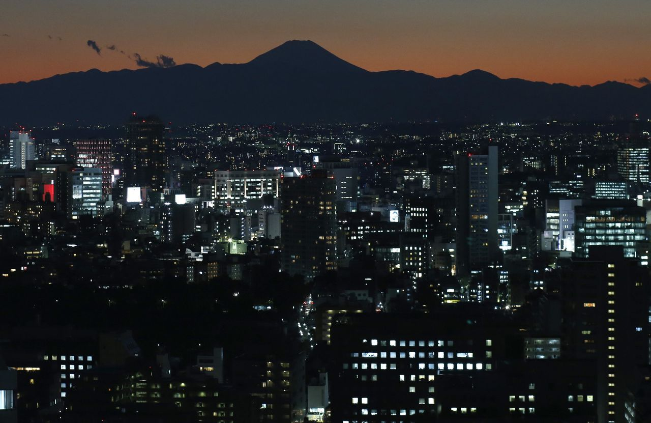 The silhouette of Japan's highest Mt. Fuji is seen beyond buildings in Tokyo in this November 15, 2012 file photo. Two U.S. billionaires are betting on rival cities, Tokyo and Osaka, to be the first in Japan to open casino resorts - once the government gives the go-ahead to legalise gambling. In a race for first-mover advantage, 76-year-old Chicago real estate mogul Neil Bluhm has set his sights on the southern commercial hub of Osaka, while Las Vegas gaming tycoon Sheldon Adelson, four years his senior, is putting his weight behind a Tokyo flagship resort. REUTERS/Toru Hanai/Files (JAPAN - Tags: BUSINESS CITYSPACE ENVIRONMENT)