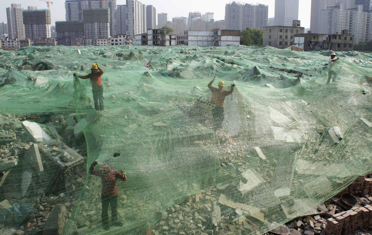 Workers set up dust screen on a demolition site in Xi'an, Shaanxi province, April 27, 2013. According to local media, along with the city's recent environment protection acts, construction sites are required to take measures controlling dust in order to improve air quality. Picture taken April 27, 2013. REUTERS/Stringer (CHINA - Tags: BUSINESS ENVIRONMENT CONSTRUCTION TPX IMAGES OF THE DAY) CHINA OUT. NO COMMERCIAL OR EDITORIAL SALES IN CHINA