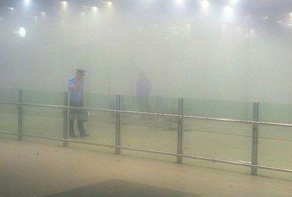 Een agent staat bij de gate van Terminal 3 op het vliegveld van Beijing nadat de man in een rolstoel een bom liet ontploffen waarbij hij zichzelf verwondde.