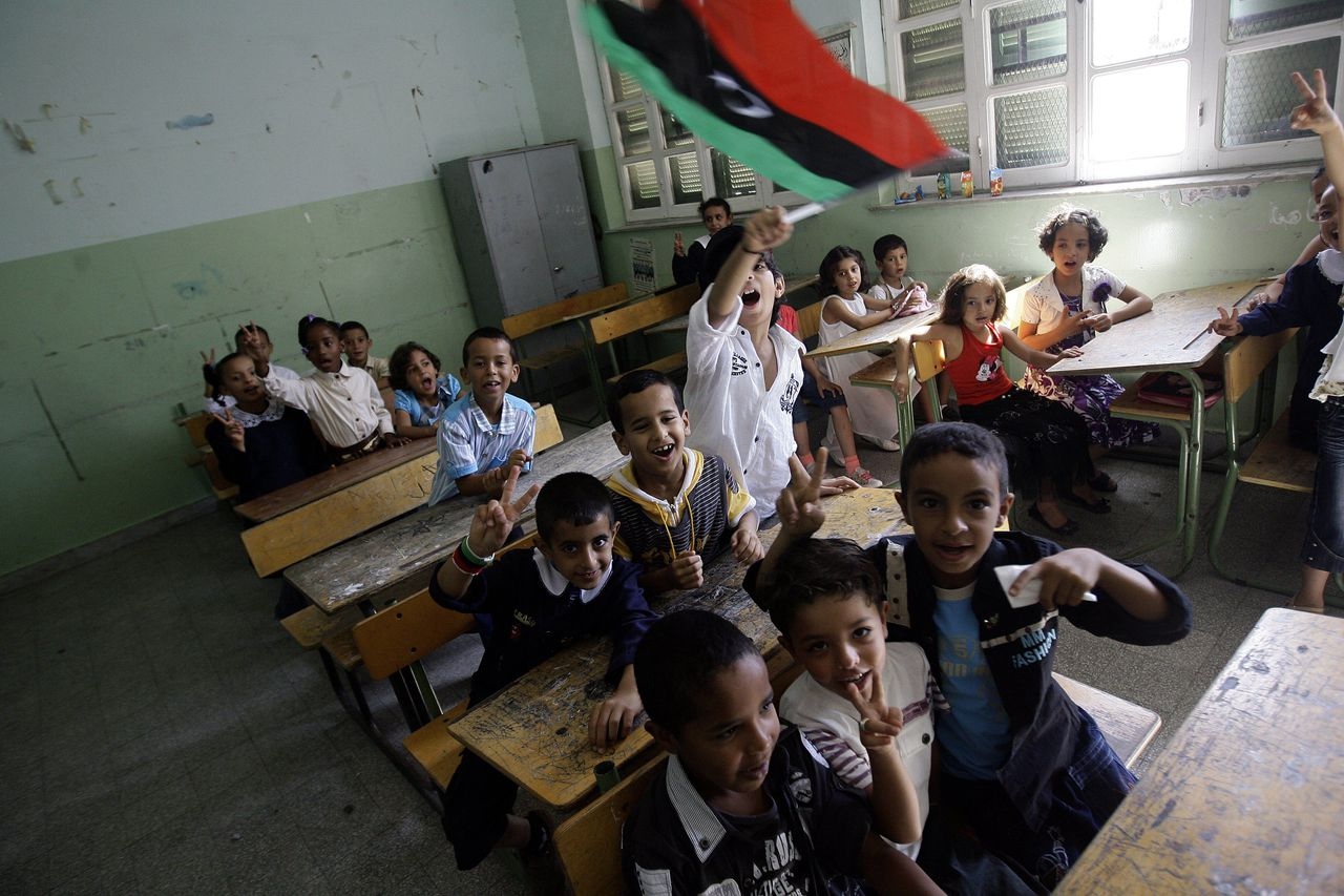 De scholen beginnen weer in Tripoli. Een leerling laat de vlag van de pre-Gaddafi monarchie wapperen. Foto AFP A student waves the flag of Libya's former monarchy, which was adopted by anti-Kadhafi forces as their banner, at a classroom in Tripoli on September 18, 2011 as schools in the Libyan capital are replacing repeated oaths of allegiance to the autocratic Guide, Moamer Kadhafi, with lessons in democracy. AFP PHOTO/JOSEPH EID