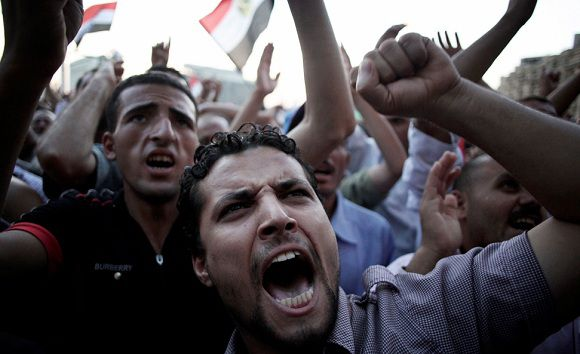 Caption: Egyptian men chant anti-Supreme Council for the Armed Forces (SCAF) slogans in Tahrir Square in Cairo, Egypt, Thursday, 21 June, 2012. Authorities delayed Thursday's planned announcement of the winner of Egypt's presidential election. Hundreds of Brotherhood supporters camped out in Cairo's Tahrir Square on Wednesday night, denouncing the ruling military and vowing to stay in place until the parliament, which was dissolved last week on a court order, is reinstated. (AP Photo/Manu Brabo)