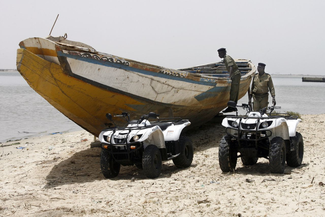 Senegalese agenten inspecteren een vermoedelijk voor mensensmokkel bestemde boot. Foto AFP Senagalese police, equipped with four-wheeled motorbikes, inspect 27 May 2007 a suspicious boat during a patrol on a beach near the northern city of Saint-Louis. Since July 2006, the Saint-Louis police force sends men on patrol on the beach as part of the Frontex European surveillance pact pased with Senegal, which allies police, gendarmes, cutoms officers and navy units, to drive would-be clandestine immigrants off the beach. AFP PHOTO GEORGES GOBET TO GO W/ AFP STORY IN FRENCH BY Coumba SYLLA