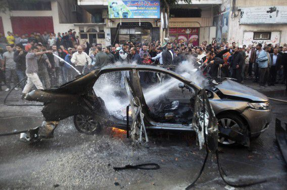 Palestijnen blussen de brandende auto waarin Hamas-chef Ahmed Jabari om het leven kwam. De auto werd getroffen door een Israëlische luchtaanval. Foto Reuters / Ali Hassan nians extinguish a fire after an Israeli air strike on a car in Gaza City November 14, 2012. Hamas's military chief was killed when his car was hit by an Israeli airstrike on Wednesday, the Palestinian Islamist group said, with multiple Israeli attacks rocking the Gaza Strip. Hamas said Ahmed Al-Jaabari, who ran the organisation's armed wing, the Izz el-Deen Al-Qassam, died along with a passenger after their car was targeted by an Israeli missile. REUTERS/Ali Hassan (GAZA - Tags: POLITICS CIVIL UNREST TPX IMAGES OF THE DAY)