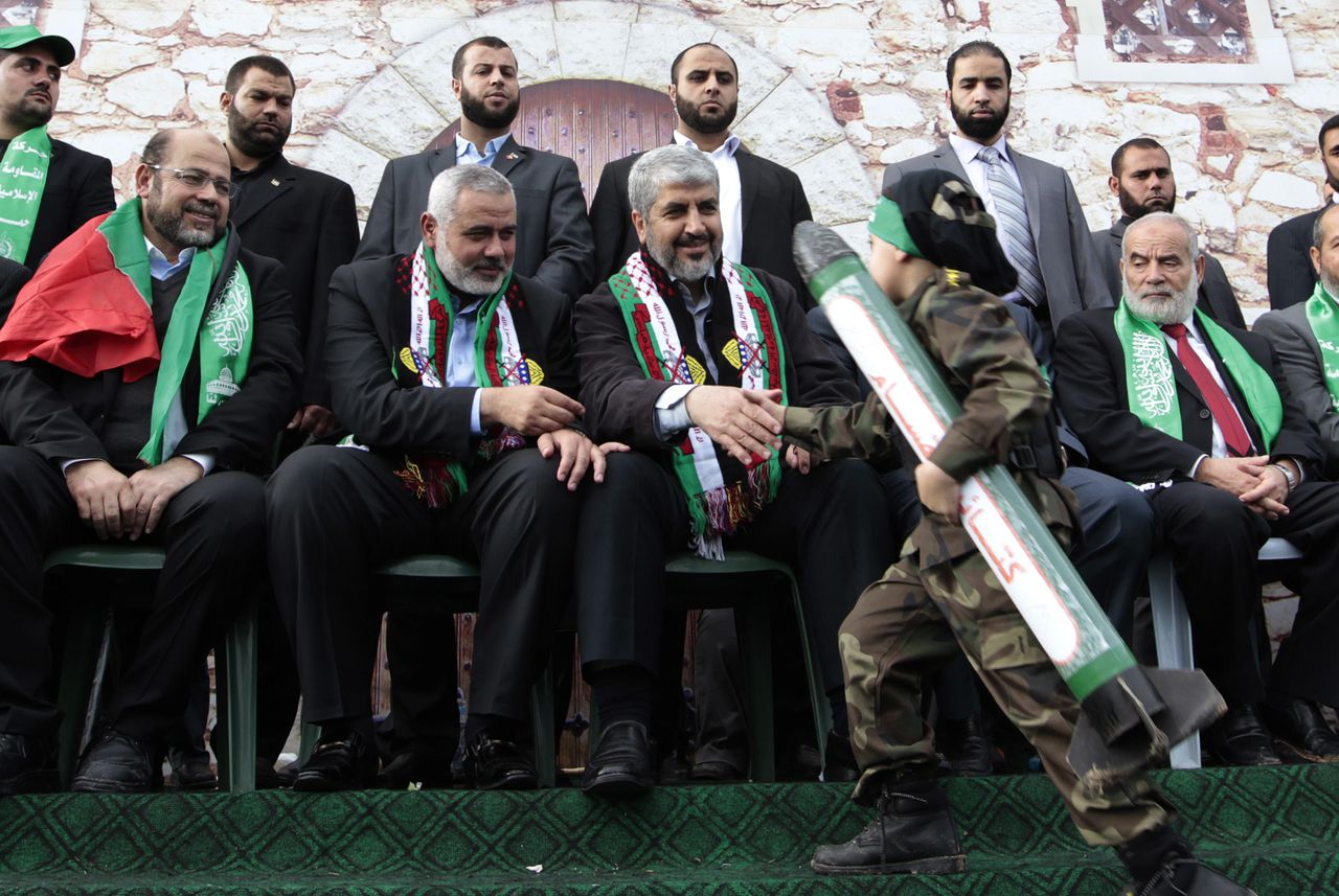 A Palestinian boy wearing a military suit shakes hands with Hamas chief Khaled Meshaal during a rally marking the 25th anniversary of the founding of Hamas, in Gaza City December 8, 2012. Meshaal, making his first ever visit to the Gaza Strip, vowed on Saturday never to recognise Israel and said his Islamist group would never abandon its claim to all Israeli territory. REUTERS/Ahmed Jadallah (GAZA - Tags: POLITICS ANNIVERSARY CIVIL UNREST TPX IMAGES OF THE DAY)