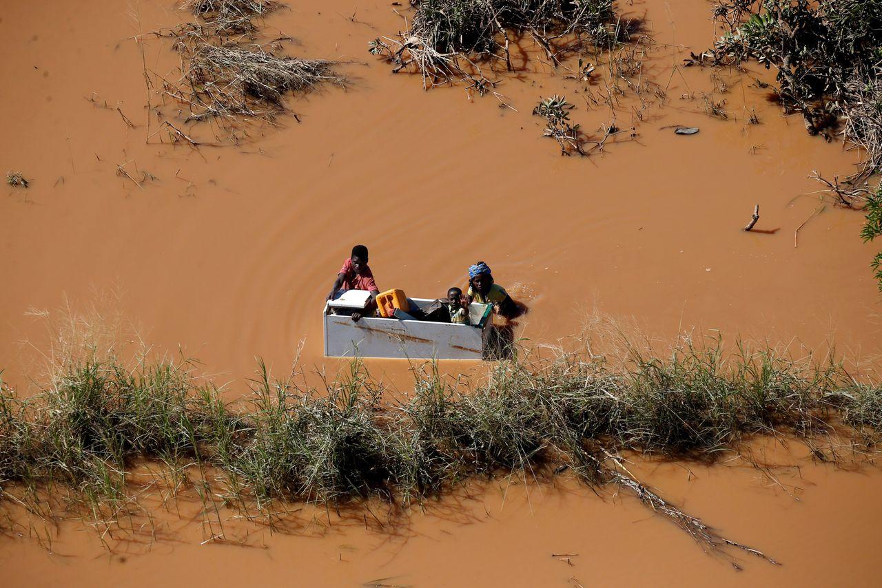 Ouders brengen hun kind in veiligheid in een drijvende koelkast na de overstromingen door cycloon Idai in Mozambique.