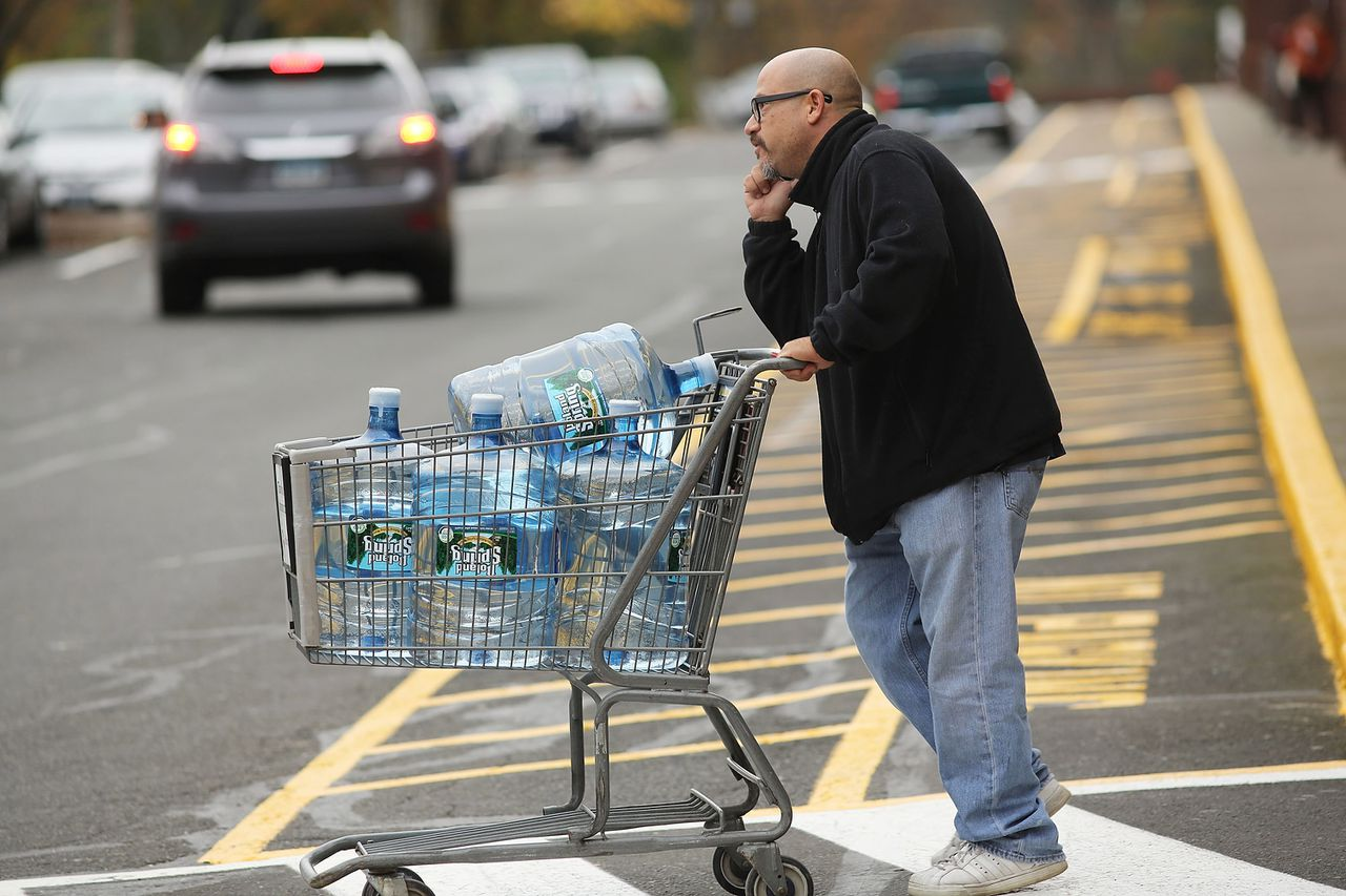 WESTPORT, CT - OCTOBER 28: A man walks out of a store with a shoping cart of water as people prepare for Hurricane Sandy on October 28, 2012 in Westport, Connecticut. The storm, which could affect tens of millions of people in the eastern third of the U.S., is expected to bring days of rain, high winds and possibly heavy snow in parts of Ohio and West Virginia. New York Governor Andrew Cuomo announced that New York City will close its bus, subway and commuter rail service Sunday evening ahead of the storm. Spencer Platt/Getty Images/AFP == FOR NEWSPAPERS, INTERNET, TELCOS & TELEVISION USE ONLY ==