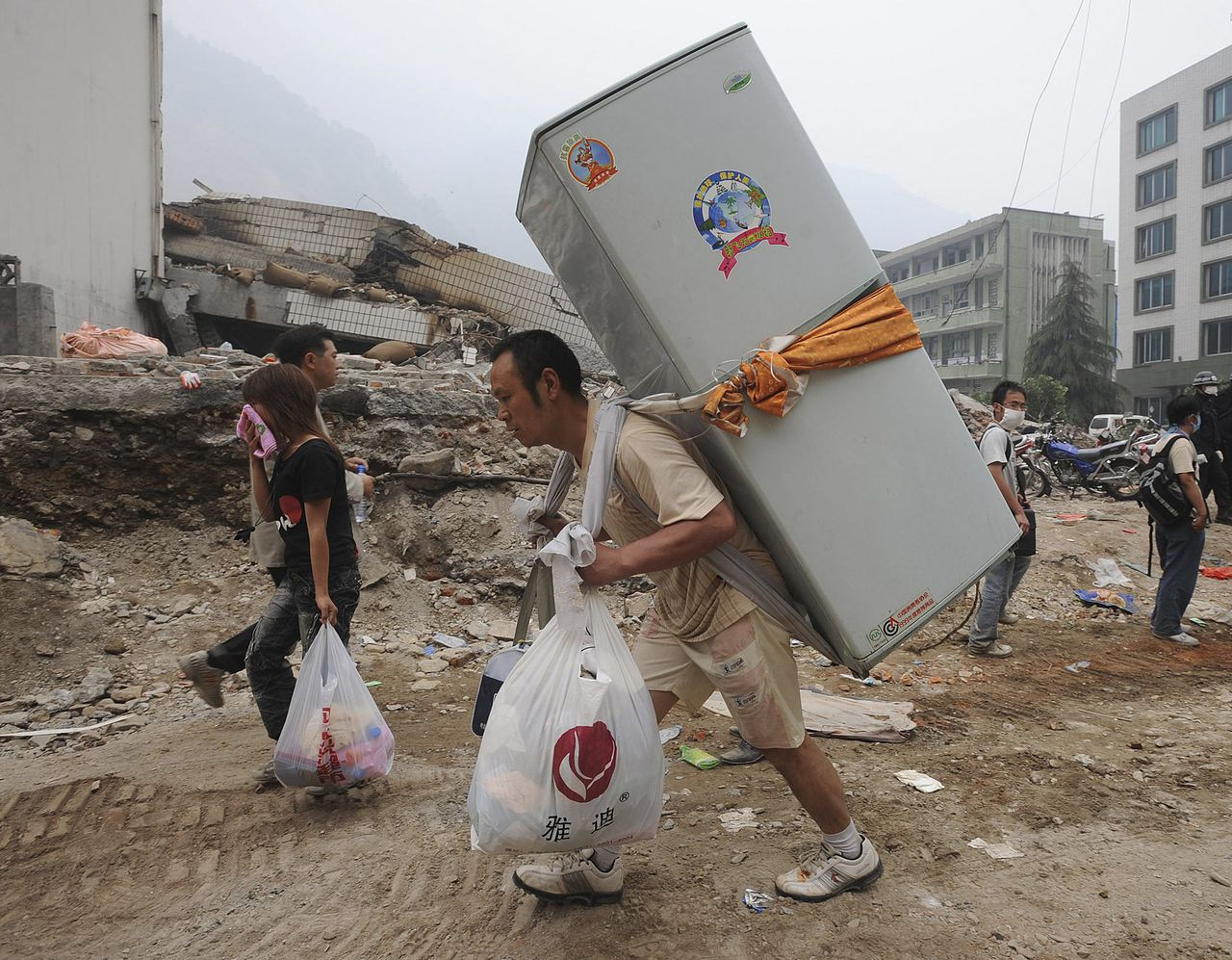 Overlevers van de aardbeving in China lopen soms dagen met hun bezittingen op hun rug. Foto Reuters An earthquake survivor carries a refrigerator on his back in Beichuan, Sichuan province May 17, 2008. Picture taken May 17, 2008. REUTERS/Jianan Yu (CHINA)